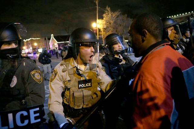 Police officers confront protesters after the announcement of the grand jury decision not to indict police officer Darren Wilson in the fatal shooting of Michael Brown, an unarmed black 18-year-old, Monday, Nov. 24, 2014, in Ferguson, Mo. (AP Photo/David Goldman)